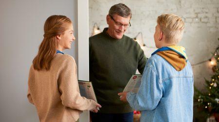 Kaksi partiolaista myymässä adventtikalenteria ostajalle ovensuussa