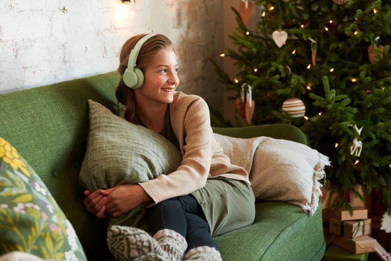 lapsi jouluisella sohvalla kuulokkeet päässään