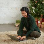 henkilö kannettavan tietokoneen kanssa lattialla jouluisessa miljöössä