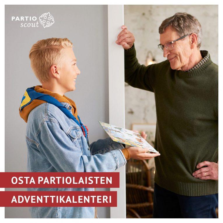 Partiolainen esittelee partiolaisten adventtikalenteria ostajalle ovensuussa
