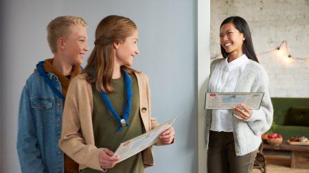 Partiolaiset adventtikalenterin kanssa ovensuussa ja iloinen ostaja kalenteri kädessään