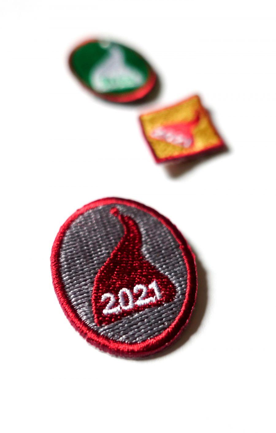 Kolme kangasmerkkiä, joissa tonttulakki ja vuosiluku 2021. Partiolaisten tonttumerkit.