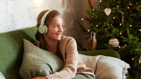tyttö sohvalla kuulokkeet päässään ja taustalla joulukuusi